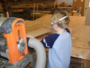 Adam takes the legs from the planer when they come out