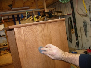 Sanding the cabinet with steel wool