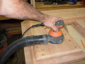 Sanding down the dried wood filler