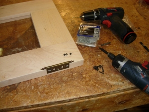 Attaching the hinges to the doors