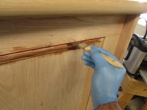 Using a brush to stain the tight spots